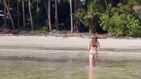Jonge vrouw die in bikini bij het zeewater op tropisch palmenlandschap bij exotisch strand lopen Achtermeningsvrouw in zwempak stock footage