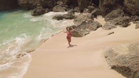Jonge vrouw die in bikini op zandig strand op overzeese golven en rotsachtig klippenlandschap lopen Satellietbeeld van aantrekkel stock videobeelden