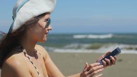 Jonge vrouw die in bikini selfie op smartphone maken, die foto op zandig strand delen stock videobeelden