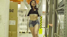 Jonge vrouw die binnen een opslagpakhuis dansen stock video