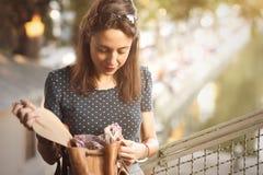Jonge vrouw die binnen haar zak kijken royalty-vrije stock afbeeldingen