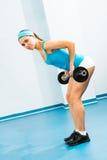 Jonge vrouw die binnen lichaam-bouwend de Gymnastiek doet Stock Afbeeldingen