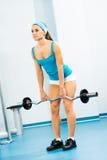 Jonge vrouw die binnen lichaam-bouwend de Gymnastiek doet Stock Foto
