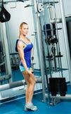 Jonge vrouw die binnen lichaam-bouwend de Gymnastiek doet Stock Fotografie