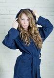 Jonge vrouw die in blauwe badstof robe de camera bekijken royalty-vrije stock afbeelding