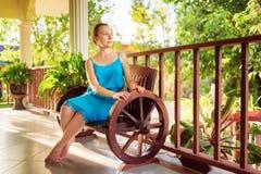 Jonge vrouw die in blauwe kleding binnenshuis terras ontspannen stock fotografie