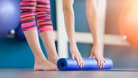 Jonge vrouw die blauwe yoga of geschiktheidsmat na het uitwerken vouwen royalty-vrije stock foto's