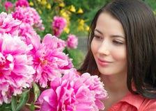Jonge vrouw die bloemenpioenen bekijken stock fotografie