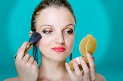 Jonge vrouw die Blush toepassen Stock Foto