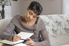 Jonge Vrouw die in Boek schrijft Royalty-vrije Stock Afbeeldingen
