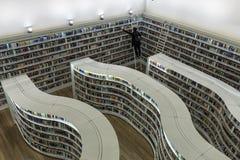 Jonge vrouw die boeken van de gebogen plankenbibliotheek trekken bij Bibliotheek bij Boomgaardwandelgalerij royalty-vrije stock foto