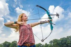Jonge vrouw die boogschieten met samenstellingsboog en pijl schieten Royalty-vrije Stock Foto's