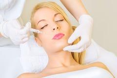 Jonge vrouw die botox injectie ontvangen stock afbeelding