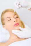 Jonge vrouw die botox injectie in voorhoofd ontvangen royalty-vrije stock afbeeldingen