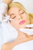 Jonge vrouw die botox injectie in voorhoofd ontvangen stock foto's
