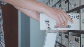 Jonge vrouw die brievenbus controleren bij flatgebouw met koopflats, binnen stock footage