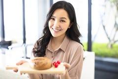 Jonge vrouw die brood in keuken tonen royalty-vrije stock foto