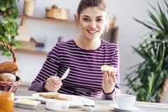 Jonge vrouw die brood met boter eten royalty-vrije stock foto's
