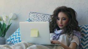 Jonge vrouw die browser die op laptop doorbladeren in het bed in een slaapruimte liggen stock videobeelden