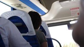 Jonge vrouw die in bus reizen die met reizigers passengeron daarna zetel spreken stock footage