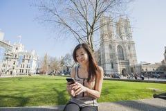 Jonge vrouw die celtelefoon met behulp van tegen de Abdij van Westminster in Londen, Engeland, het UK Royalty-vrije Stock Afbeeldingen