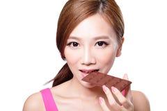 Jonge vrouw die chocolade eten Stock Foto's