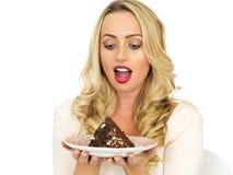 Jonge vrouw die chocoladecake eten stock afbeeldingen