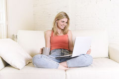 Jonge vrouw die comfortabel op huisbank die Internet gebruiken in laptop computer gelukkig glimlachen liggen Royalty-vrije Stock Afbeelding