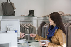 Jonge vrouw die creditcard geven aan kassier Royalty-vrije Stock Fotografie