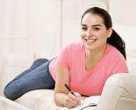 Jonge vrouw die in dagboek op laag schrijft Stock Foto