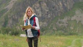 Jonge vrouw die in de bergen met een kaart reizen Het concept van de vrijheid meisjesreiziger met een kaart op de achtergrond van stock footage