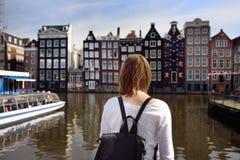 Jonge vrouw die de beroemde dansende huizen van Amsterdam op zonnige dag bekijken stock afbeeldingen