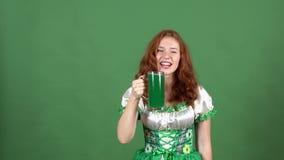 Jonge vrouw die de Dag van Heilige Patrick ` s op groene muur vieren die de traditionele toejuichingen van het kledings groene bi stock videobeelden