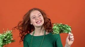 Jonge vrouw die de dag van heilige Patrick ` s op oranje muur vieren die met pom dansen poms stock footage