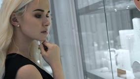 Jonge vrouw die de de winkelshowcase en juwelen bekijken om het binnen te bekijken de dichtere, mooie mannequin van het studenten stock video