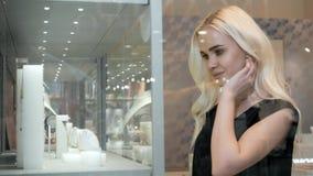 Jonge vrouw die de de winkelshowcase en juwelen bekijken om het binnen te bekijken de dichtere, mooie mannequin van het studenten stock footage