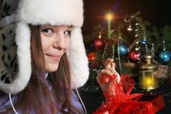 Jonge Vrouw die de Gift van Kerstmis openvouwt stock afbeelding
