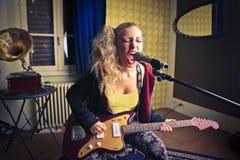 Jonge vrouw die de gitaar en het zingen spelen royalty-vrije stock foto's