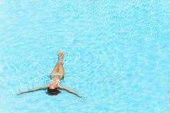 Jonge vrouw die in de glasheldere pool zwemmen royalty-vrije stock afbeeldingen