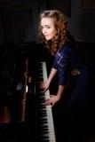 Jonge vrouw die de grote piano spelen Stock Foto's