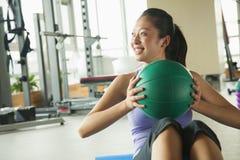 jonge vrouw die in de gymnastiek uitoefenen Stock Afbeeldingen