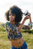 Jonge vrouw die de kam van het afrohaar gebruikt stock fotografie