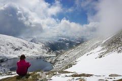 Jonge vrouw die de mening in de bergen bewonderen stock afbeeldingen