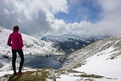 Jonge vrouw die de mening in de bergen bewonderen royalty-vrije stock afbeelding