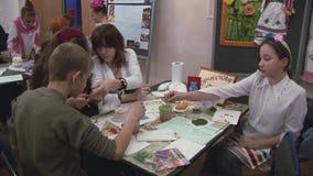Jonge vrouw die de met de hand gemaakte vaas van de tienerjarenverf van klei helpen bij lijst festival verwezenlijking stock videobeelden