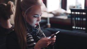 Jonge vrouw die de mobiele telefoon met behulp van, die terwijl het zitten in café met de elektronische post versturen Zijnd een stock videobeelden