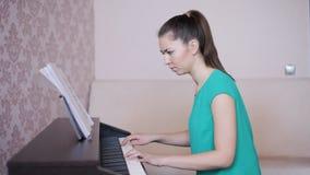 Jonge vrouw die de piano leren te spelen stock video