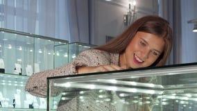 Jonge vrouw die in de showcase de juwelenopslag bekijken stock footage