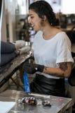 Jonge vrouw die de de tatoegeringsmachine en inkt voorbereiden royalty-vrije stock afbeeldingen