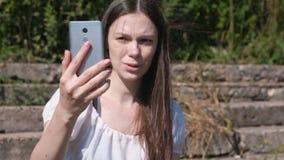 Jonge vrouw die de telefoon bij het videopraatje, spreken en glimlachen uitnodigen stock video